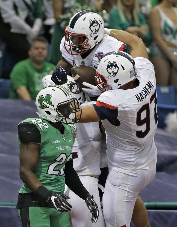 Connecticut running back Ron Johnson (3) celebrates with Steve Hashemi (97) in front of Marshall linebacker D.J. Hunter (22) after scoring during the first quarter of the St. Petersburg Bowl NCAA college football game, Saturday, Dec. 26, 2015, in St. Petersburg, Fla. (AP Photo/Chris O'Meara)
