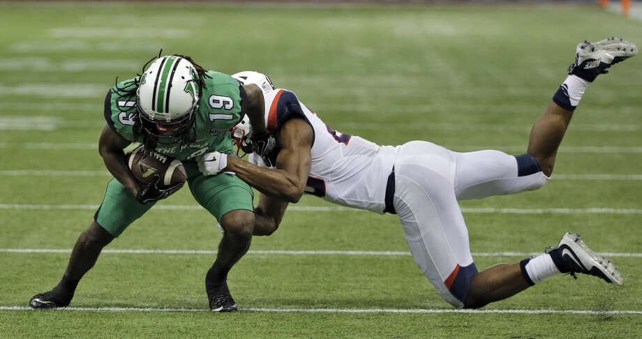 Marshall wide receiver Deandre Reaves (19) eludes a diving tackle by Connecticut safety Obi Melifonwu (20) during the first quarter of the St. Petersburg Bowl NCAA college football game Saturday, Dec. 26, 2015, in St. Petersburg, Fla. (AP Photo/Chris O'Meara)
