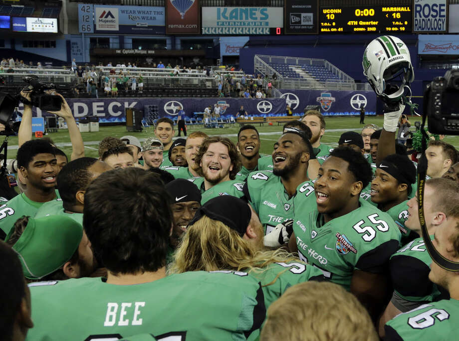 Marshall players celebrate their 16-10 win over Connecticut during the St. Petersburg Bowl NCAA college football game Saturday, Dec. 26, 2015, in St. Petersburg, Fla. (AP Photo/Chris O'Meara)