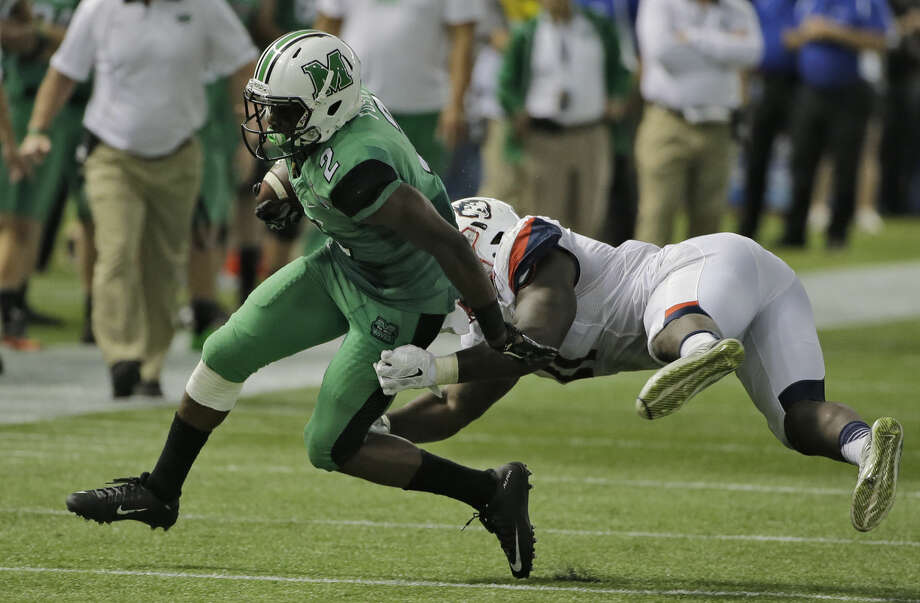 Marshall wide receiver Hyleck Foster (2) slips a tackle by Connecticut linebacker Junior Joseph (11) during the St. Petersburg Bowl NCAA college football game Saturday, Dec. 26, 2015, in St. Petersburg, Fla. (AP Photo/Chris O'Meara)