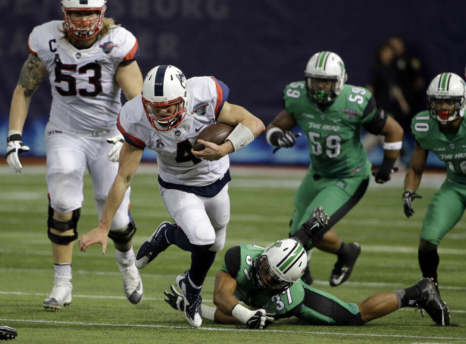 Connecticut quarterback Bryant Shirreffs (4) is tripped up by Marshall safety Chase Hancock (37) during the St. Petersburg Bowl NCAA college football game Saturday, Dec. 26, 2015, in St. Petersburg, Fla. (AP Photo/Chris O'Meara)