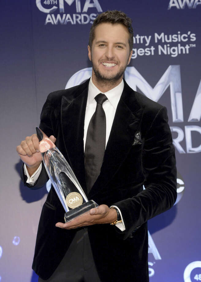 Luke Bryan poses in the press room with the award for entertainer of the year at the 48th annual CMA Awards at the Bridgestone Arena on Wednesday, Nov. 5, 2014, in Nashville, Tenn. (Photo by Evan Agostini/Invision/AP)