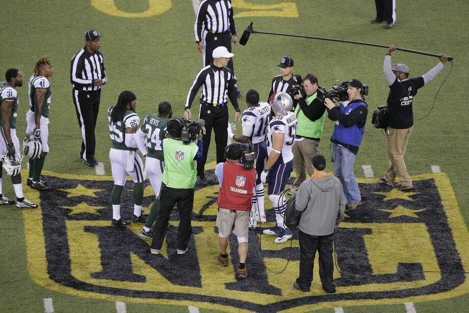 The officials meet New York Jets' Darrelle Revis (24), teammate Calvin Pryor (25) and New England Patriots' Matthew Slater (18) and teammate Rob Ninkovich (50) for the coin toss before the overtime period of an NFL football game between the New York Jets and the New England Patriots, Sunday, Dec. 27, 2015, in East Rutherford, N.J. The Jets won 26-20. (AP Photo/Peter Morgan)