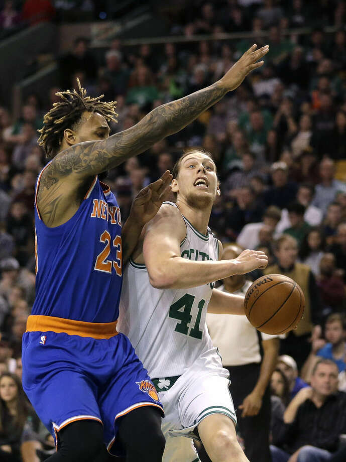 Boston Celtics center Kelly Olynyk, right, tries to drive to the basket past New York Knicks forward Derrick Williams, left, in the first quarter of an NBA basketball game Sunday, Dec. 27, 2015, in Boston. (AP Photo/Steven Senne)
