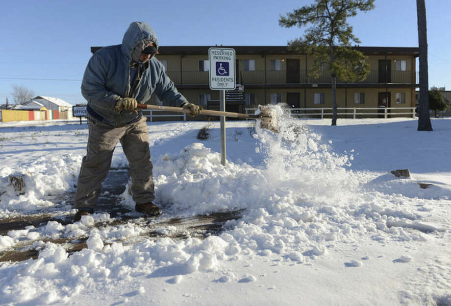 Ismael Avelar, maintenance employee for the Village Place Apartments, shovels snow Monday morning, Dec. 28, 2015, from the walkway to the apartment complex office in Odessa, Texas. As much as 7 inches of snow fell over the weekend in Odessa and many businesses and government offices were closed Monday. Avelar said he slid or became stuck four times while driving to work. (Mark Sterkel/Odessa American via AP)