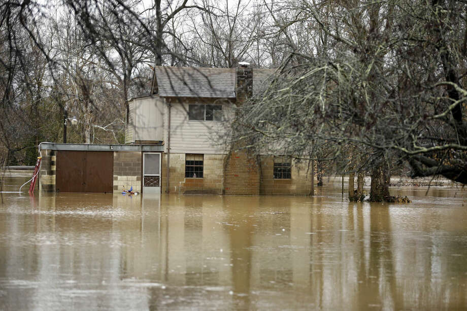 Floodwater surrounds a home Monday, Dec. 28, 2015, in Eureka, Mo. Missouri Gov. Jay Nixon has declared a state of emergency due to wide spread flooding around the state that has closed many roads after a storm system dropped more than half a foot of rain and left several dead. (AP Photo/Jeff Roberson)