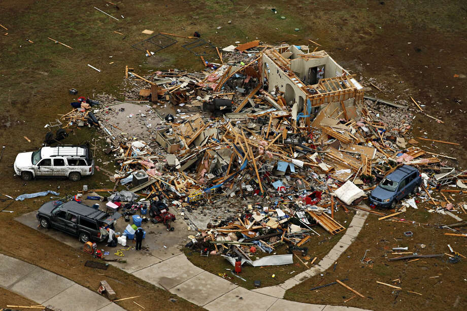 This aerial photo shows a damaged home after a tornado ripped through the area, Monday, Dec. 28, 2015 in Texas. Residents surveyed the destruction from deadly tornadoes in North Texas as the same storm system brought winter woes to the Midwest on Monday, amplifying flooding that's blamed for more than a dozen deaths and prompting hundreds of flight cancellations. At least 11 people died and dozens were injured in the tornadoes that swept through the Dallas area Saturday and caused substantial damage. (G.J. McCarthy/The Dallas Morning News via AP) MANDATORY CREDIT; MAGS OUT; TV OUT; INTERNET USE BY AP MEMBERS ONLY; NO SALES