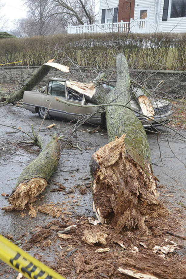 Part of a tree rests on a crushed car in Marion, Ind., after ice and high winds hit the area on Monday, Dec. 28, 2015. The storm system that spawned weekend twisters in North Texas brought winter storm woes to the Midwest on Monday and amplified flooding that's blamed for more than a dozen deaths. (Jeff Morehead/Chronicle-Tribune via AP)