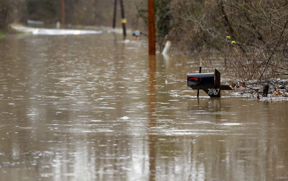 A nearly flooded mailbox sits along a flooded road Monday, Dec. 28, 2015, in Eureka, Mo. Missouri Gov. Jay Nixon has declared a state of emergency due to wide spread flooding around the state that has closed many roads after a storm system dropped more than half a foot of rain and left several dead. (AP Photo/Jeff Roberson)