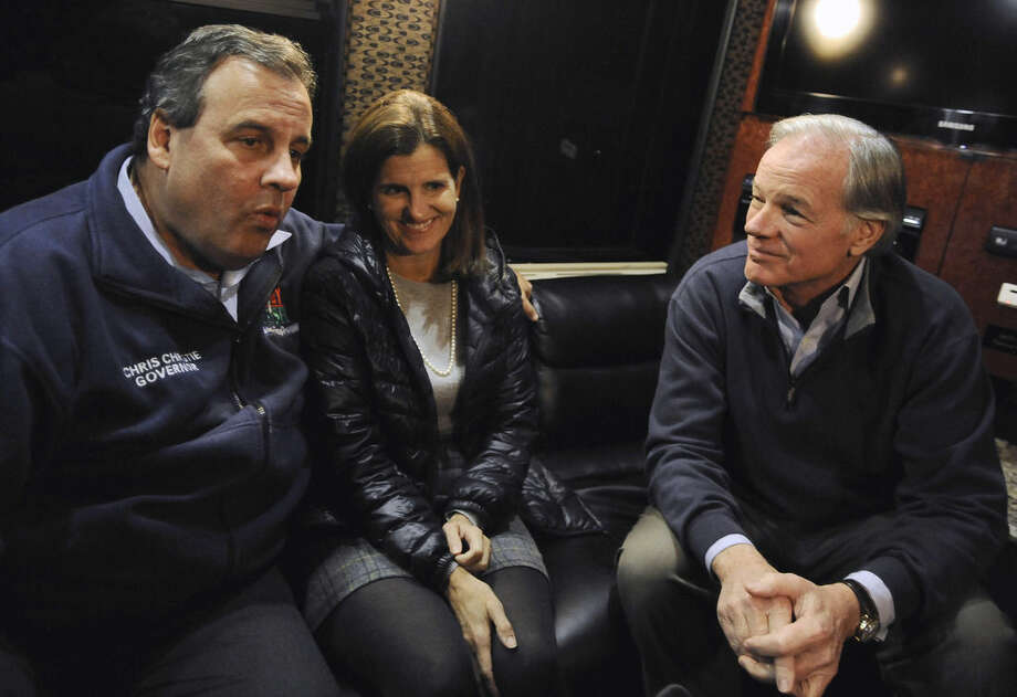 New Jersey Gov. Chris Christie, left, and Republican candidate for governor Tom Foley, right, are interviewed by The Associated Press during a bus ride to a rally, as Christie's wife Mary Pat, center, listens, Monday, Nov. 3, 2014, in East Granby, Conn. (AP Photo/Jessica Hill)