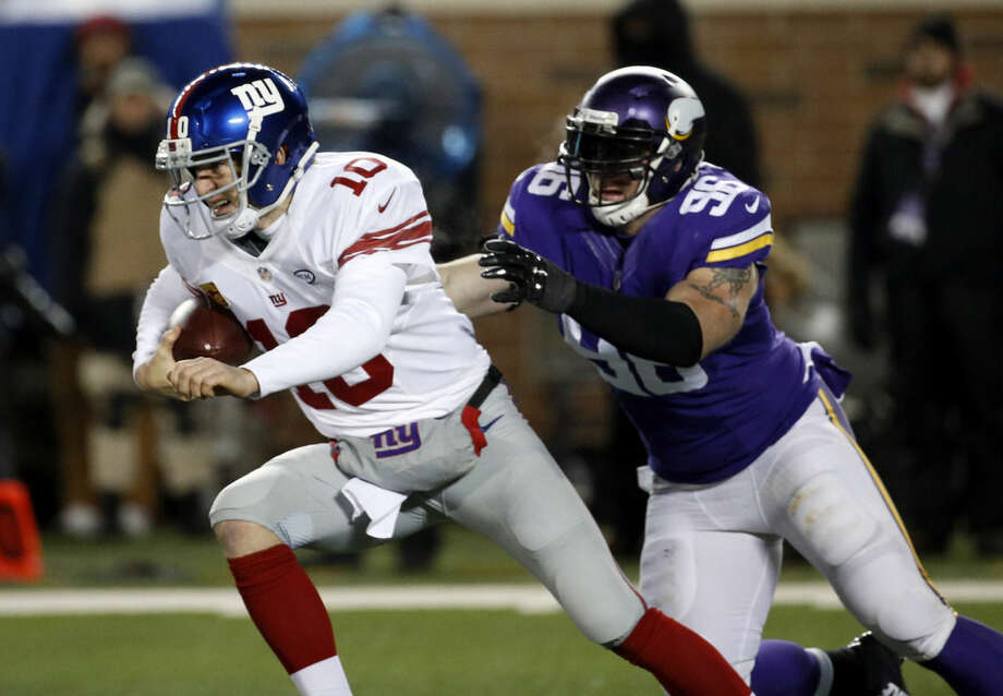 New York Giants quarterback Eli Manning (10) tries to get away from Minnesota Vikings defensive end Brian Robison (96) during the first half of an NFL football game Sunday, Dec. 27, 2015, in Minneapolis. (AP Photo/Ann Heisenfelt)