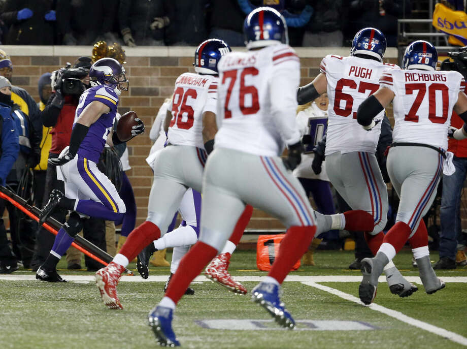 Minnesota Vikings free safety Harrison Smith, left, runs with his interception for a touchdown as he is pursued by New York Giants tight end Jerome Cunningham (86) and others during the first half of an NFL football game, Sunday, Dec. 27, 2015, in Minneapolis. (AP Photo/Ann Heisenfelt)