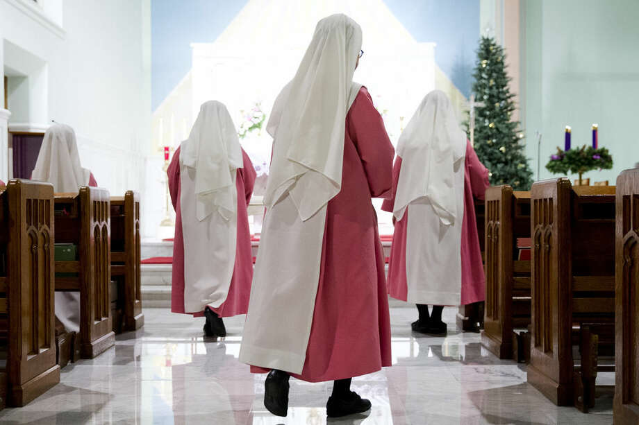 Roman Catholic Holy Spirit Adoration sisters moves from their pews after a pray service Tuesday, Dec. 22, 2015, at the Chapel of Divine Love in Philadelphia. For 100 years now, twenty-four hours a day, one of the cloistered nuns in a pink habit pray before the altar at the chapel. To address their shrinking numbers and ensure their prayers continue for another century, the Roman Catholic Holy Spirit Adoration sisters have begun quietly reaching out, seeking to grow their order while carefully maintaining their secluded life. (AP Photo/Matt Rourke)