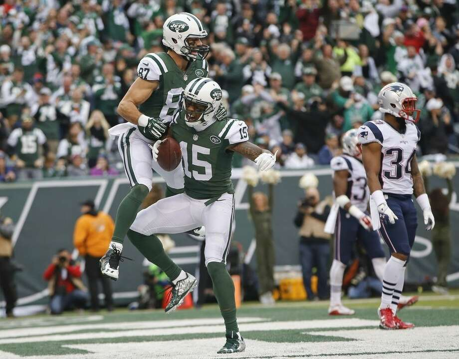 CORRECTS TO SECOND HALF NOT FIRST New York Jets wide receiver Brandon Marshall (15) and Eric Decker (87) celebrate a touchdown as New England Patriots' Leonard Johnson (34) looks on during the second half of an NFL football game, Sunday, Dec. 27, 2015, in East Rutherford, N.J. (AP Photo/Kathy Willens)