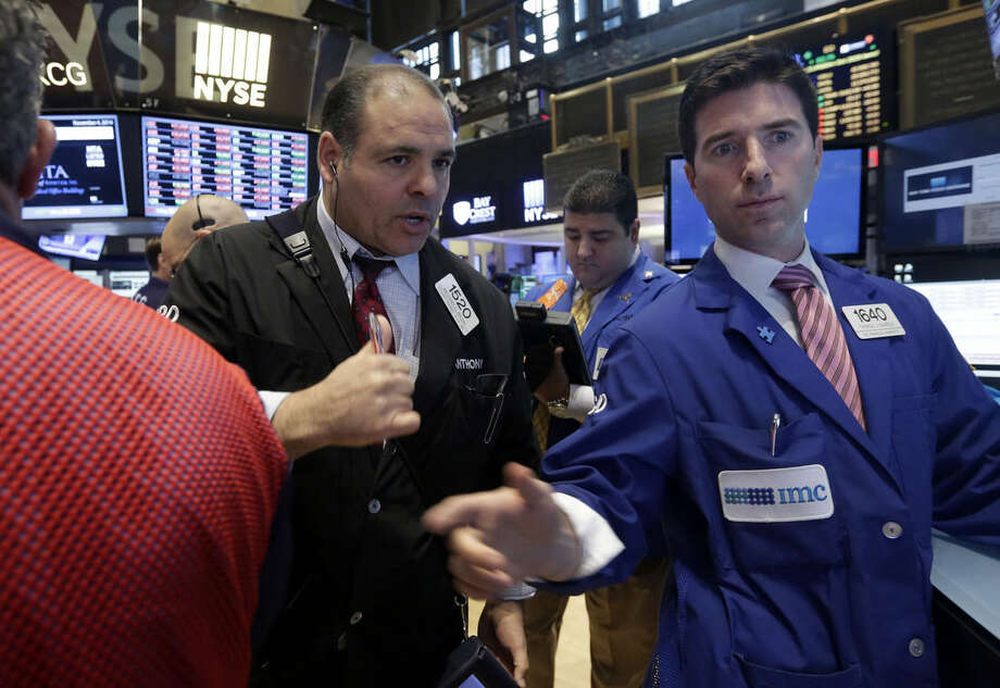 Trader Anthony Riccio, left, and specialist Thomas McArdle, right, work on the floor of the New York Stock Exchange, Tuesday, Nov. 4, 2014. Stocks edged lower on Tuesday, led by a drop in energy stocks as the price of oil fell to its lowest in four years following reports that Saudi Arabia has cut its prices to the U.S. (AP Photo/Richard Drew)
