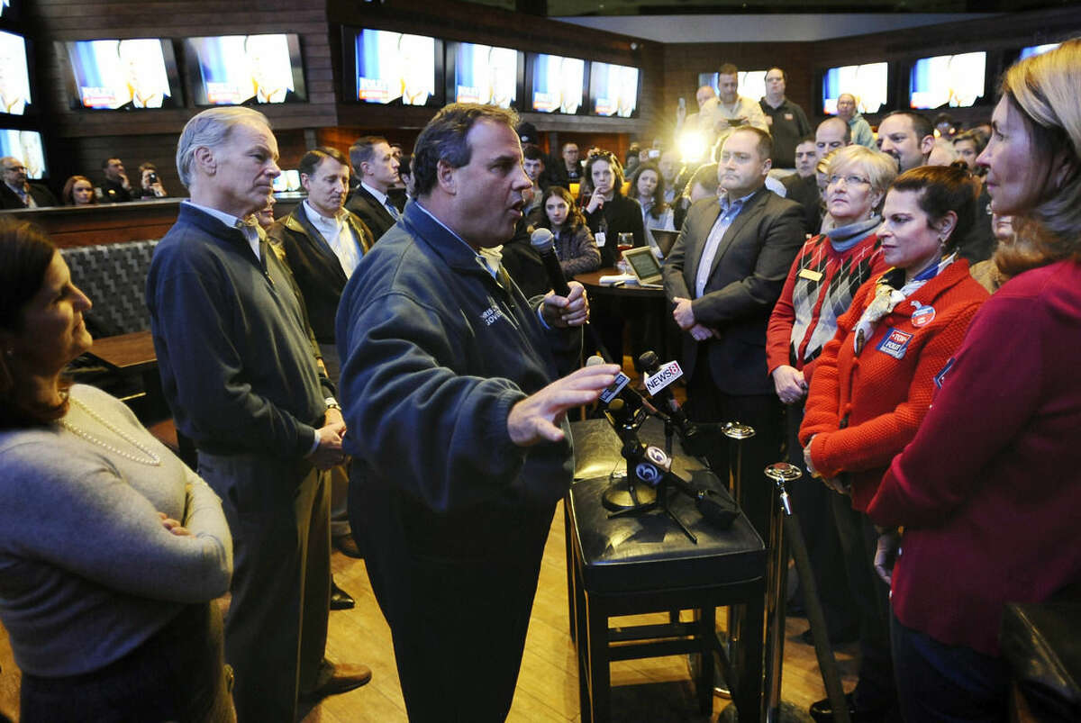 New Jersey Gov. Chris Christie, center, speaks to supporters, as Republican candidate for Connecticut governor Tom Foley looks on during a rally for Foley, Monday, Nov. 3, 2014, in Windsor Locks, Conn. (AP Photo/Jessica Hill)