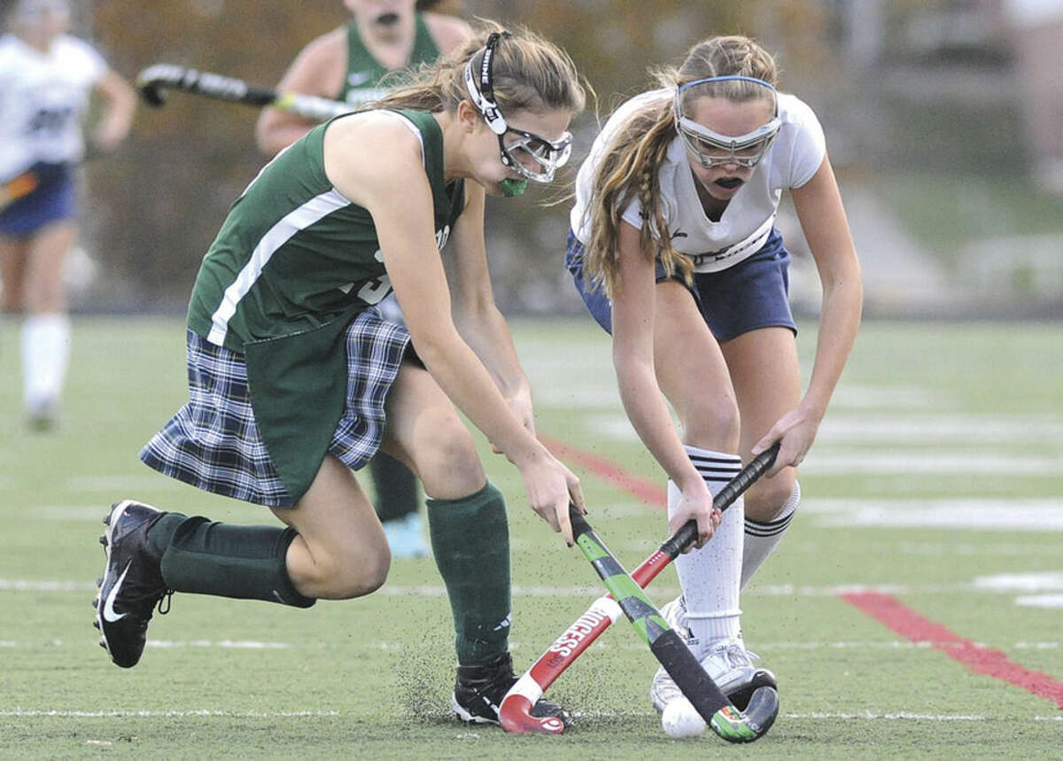 Hour photo/Matthew Vinci Wilton's Bridget Ward, right, and Guilford's Abbey Miranker fight for a ball during Tuesday's state tournament game.
