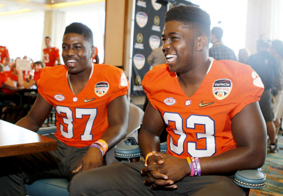 Clemson linebacker Judah Davis (37) and his twin brother, Clemson linebacker J.D. Davis (33), are interviewed during Orange Bowl media day at Sun Life Stadium Tuesday, Dec. 29, 2015, in Miami Gardens, Fla. Clemson is scheduled to play Oklahoma in the Orange Bowl NCAA college football game on New Year's Eve. (AP Photo/Joe Skipper)