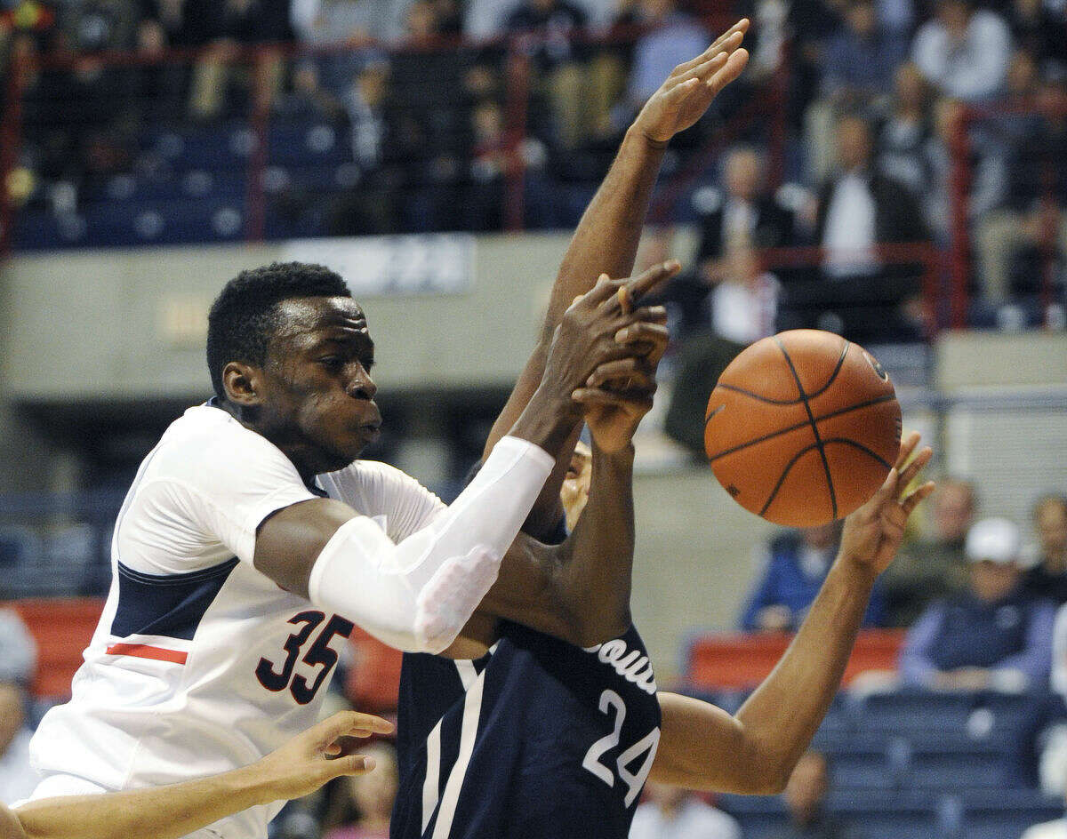 Connecticut's Amida Brimah (35) scrambles for a rebound with Southern Connecticut's Deshawn Murphy (24) during the first half of an NCAA college basketball game exhibition game in Storrs, Conn., on Tuesday, Nov. 4, 2014. (AP Photo/Fred Beckham)