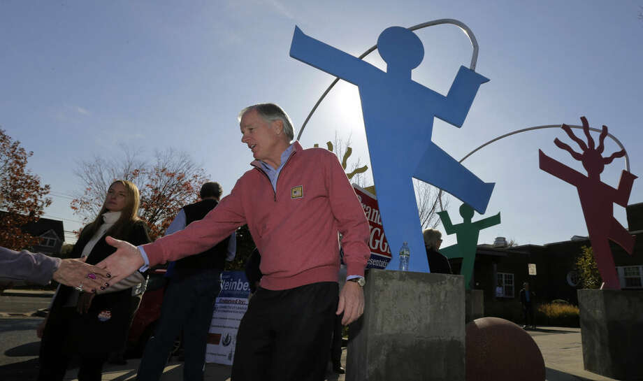 Republican candidate for governor Tom Foley shakes hands with a voter while campaigning outside a polling place in Westport, Conn., Tuesday, Nov. 4, 2014. Foley is facing incumbent Democratic Gov. Dannel Malloy in the general election. (AP Photo/Charles Krupa)