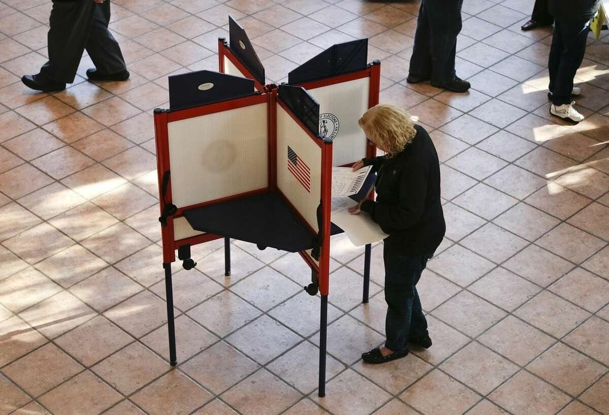 A woman prepares to mark her ballot at a polling site, Tuesday, Nov. 4, 2014, in Mount Kisco, N.Y. New Yorkers will decide to send back Gov. Andrew Cuomo for a second term. If Cuomo wins he will be the first Democratic governor since his father, Mario Cuomo, to win re-election. (AP Photo/Julie Jacobson)