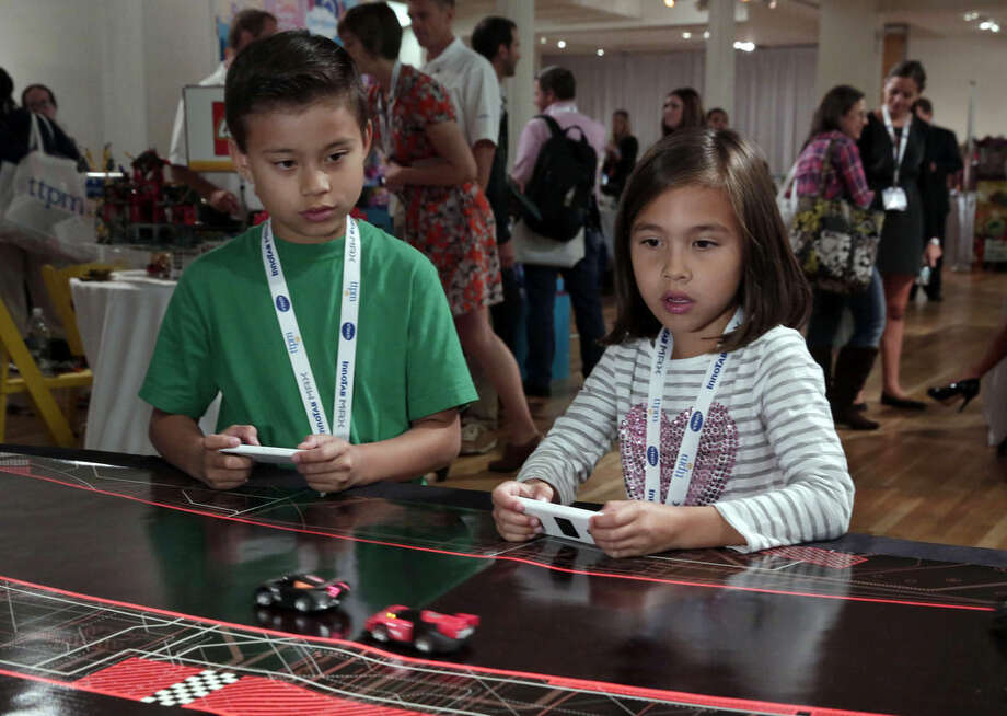 In this Oct. 1, 2014 photo, Evan and Jillian, of EvanTubeHD, test the Anki Drive battle-racing game, at the TTPM Holiday Showcase, in New York, Wednesday, Oct. 1, 2014. Evan has over 800 million views on EvanTubeHD, where he reviews toys. (AP Photo/Richard Drew)