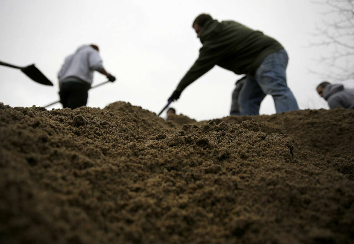 Volunteers use shovels atop a pile of sand as they help fill sandbags Tuesday, Dec. 29, 2015, in St. Louis. Flooding across Missouri has forced the closure of hundreds of roads and threatened homes. (AP Photo/Jeff Roberson)