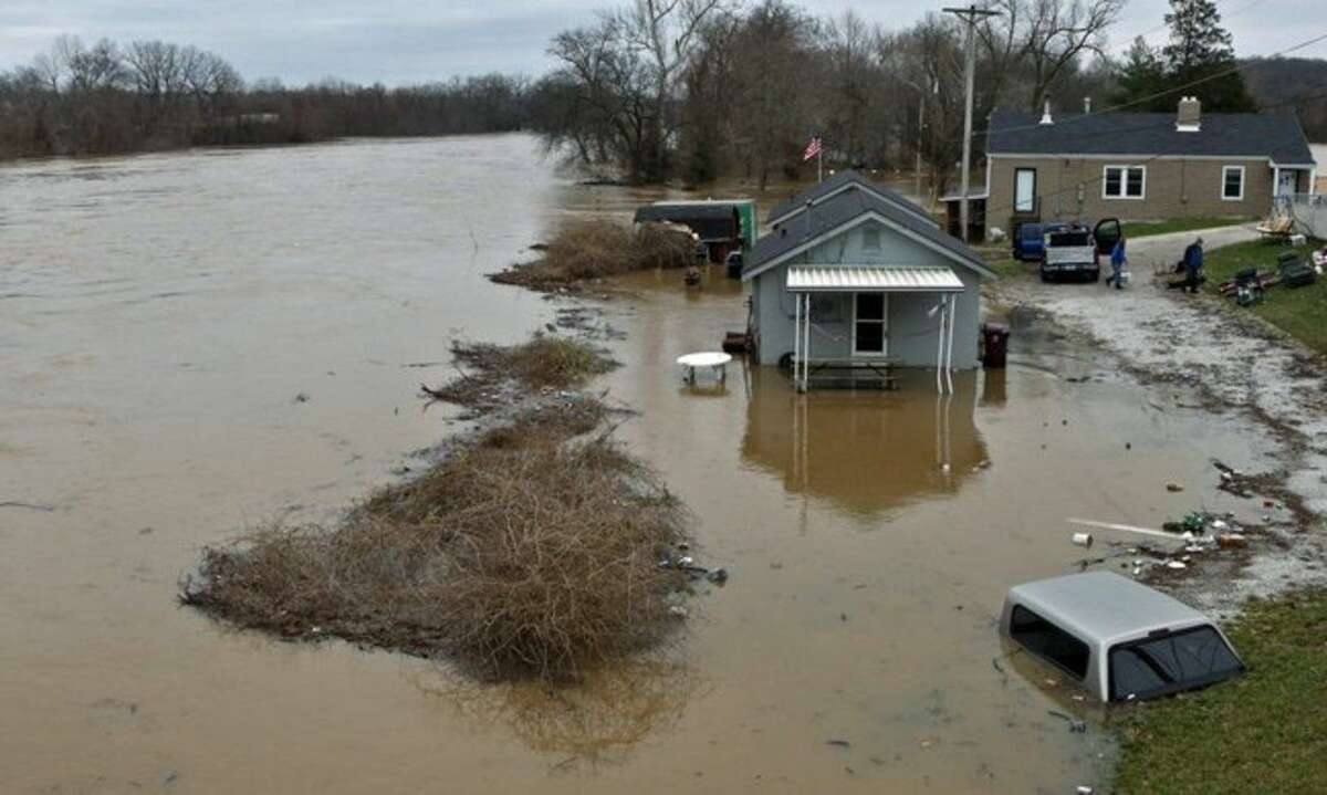 People move some of their belongings to higher ground on Tuesday, Dec. 29, 2015, as the Meramec River continues to rise next to the Gravois Road bridge in old town Fenton, Mo. Torrential rains over the past several days pushed already swollen rivers and streams to virtually unheard-of heights in parts of Missouri and Illinois. Record flooding was projected at some Mississippi River towns, and the Meramec River near St. Louis was expected to get to more than 3 feet above the previous record by late this week (J.B. Forbes /St. Louis Post-Dispatch via AP) EDWARDSVILLE INTELLIGENCER OUT; THE ALTON TELEGRAPH OUT; MANDATORY CREDIT