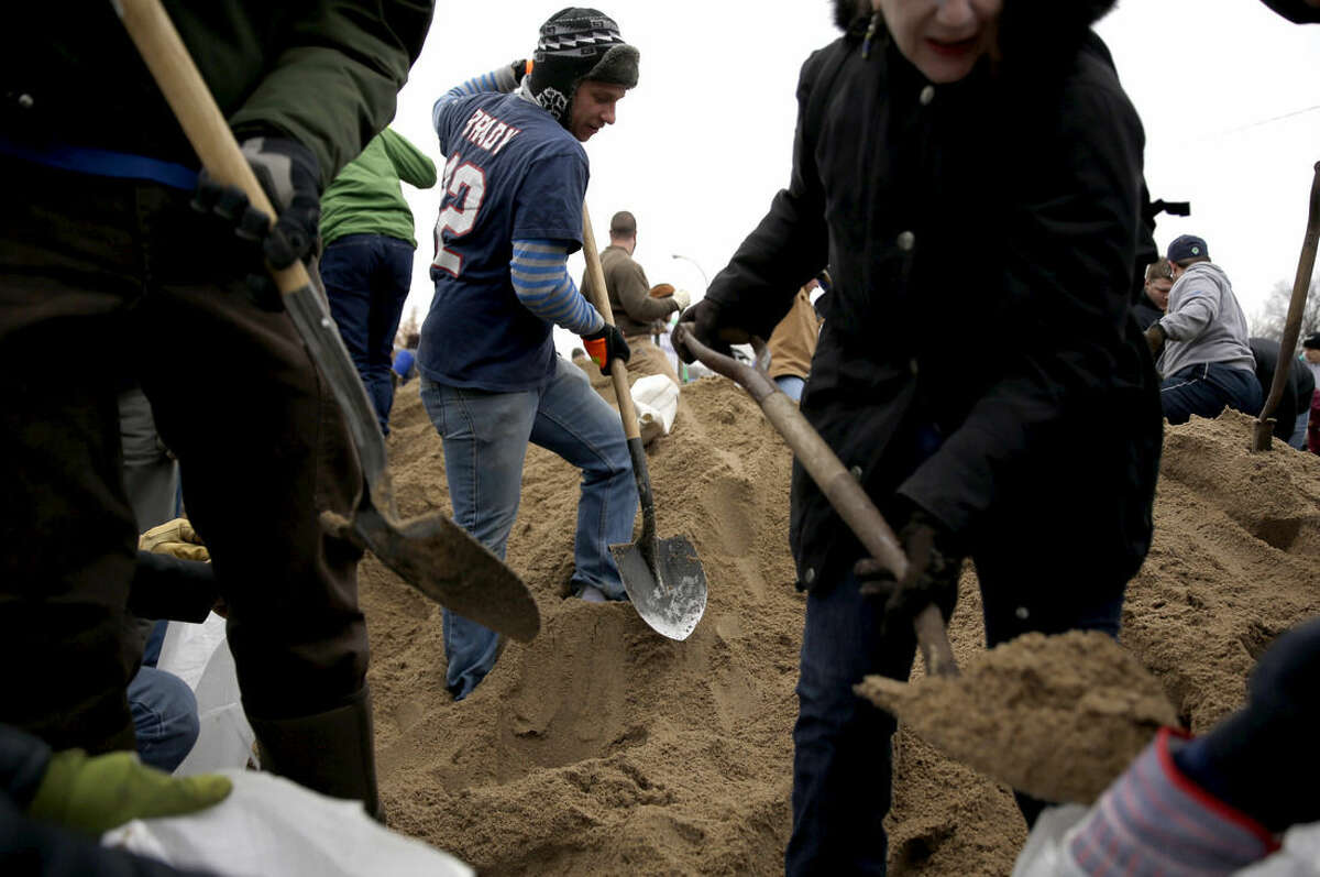 Jason Fitzgibbons, center, helps fill sandbags with other volunteers Tuesday, Dec. 29, 2015, in St. Louis. Flooding across Missouri has forced the closure of hundreds of roads and threatened homes. (AP Photo/Jeff Roberson)