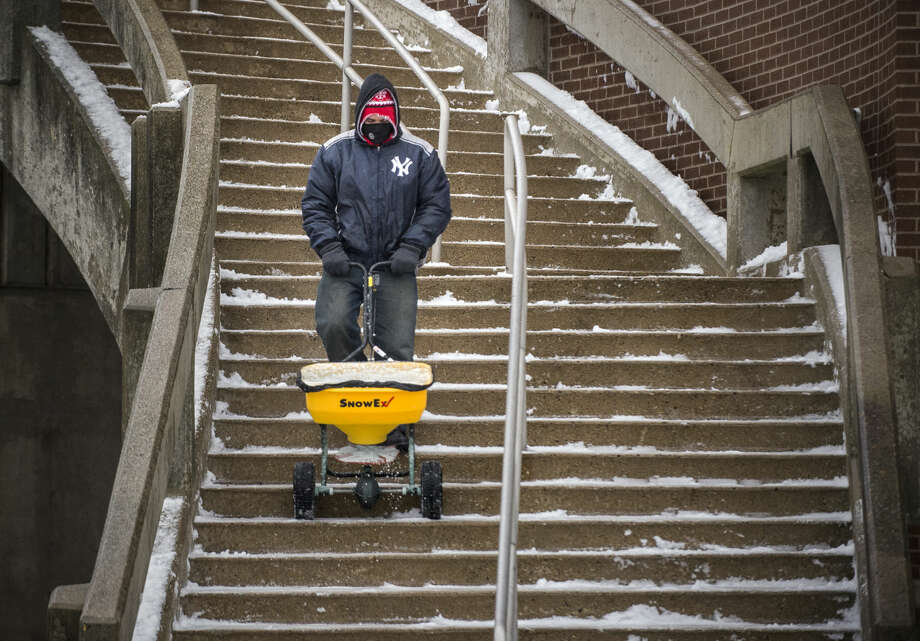 Luis Pacheco spreads salt over stairs at the University of Connecticut in Storrs, Conn., Tuesday, Dec. 29, 2015, after 1-2 inches of snow fell across the state in the first snow of the season. Connecticut State Police say troopers responded to more than 50 crashes on highways across the state during the first winter storm of the season. (Mark Mirko/Hartford Courant via AP) MANDATORY CREDIT