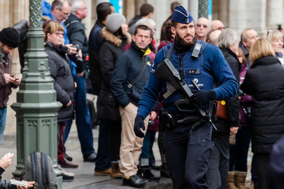 An armed police man patrols at the Grand Place in Brussels on Tuesday, Dec. 29, 2015. Two people have been arrested in Belgium on suspicion of planning attacks in Brussels during the holidays, the federal prosecutor's office said Tuesday. A source close to the investigation said the Belgian capital's main square, thronged this time of year with holiday shoppers and strollers, was one of the suspected targets. (AP Photo/Geert Vanden Wijngaert)