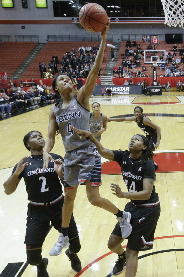 Connecticut's Moriah Jefferson (4) shoots over Cincinnati's Nikira Goings (2) and Trinity Hunter (14) during the first half of an NCAA college basketball game, Wednesday, Dec. 30, 2015, in Cincinnati. (AP Photo/John Minchillo)