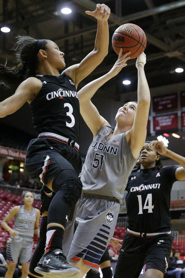 Connecticut center Natalie Butler (51) shoots against Cincinnati's Ana Owens (3) as Trinity Hunter (14) helps defend during the first half of an NCAA college basketball game, Wednesday, Dec. 30, 2015, in Cincinnati. (AP Photo/John Minchillo)
