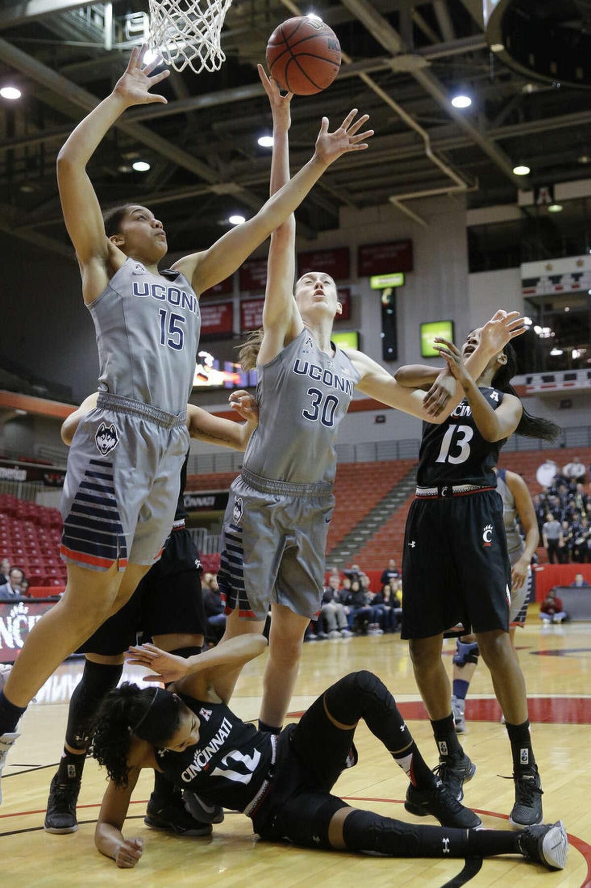Connecticut's Breanna Stewart (30) and Gabby Williams (15) reach for a rebound over Cincinnati's Alyesha Lovett (12) during the first half of an NCAA college basketball game, Wednesday, Dec. 30, 2015, in Cincinnati. (AP Photo/John Minchillo)