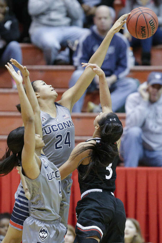 Connecticut's Napheesa Collier (24) blocks a shot by Cincinnati's Ana Owens (3) as Moriah Jefferson (4) defends during the first half of an NCAA college basketball game, Wednesday, Dec. 30, 2015, in Cincinnati. (AP Photo/John Minchillo)