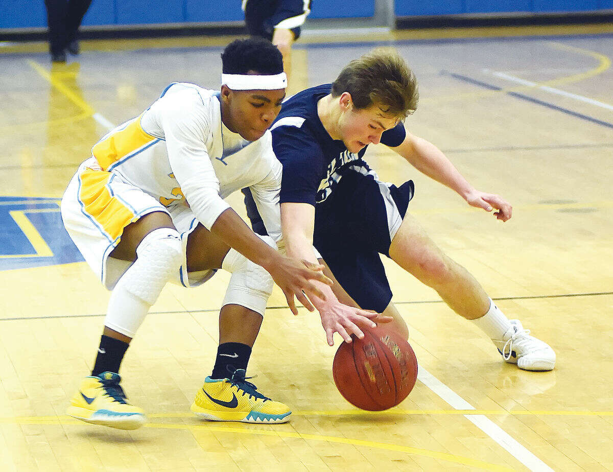 Hour photo/John Nash - Wilton's Jack Williams, right, angles himself against Kolbe Cathedral's Sam Muhammed while chasing down a loose ball during the second half of Wednesday's championship game of the Hoops for Heroes Holiday Tournament at Newtown High School.