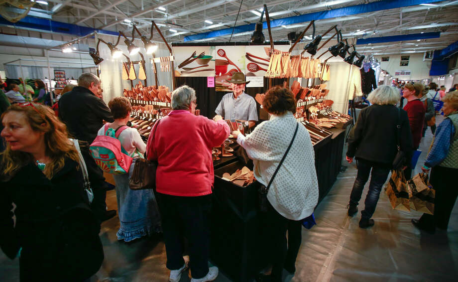 Hour photo/Chris Palermo. Shoppers visit the Jonathan Spoons booth at the CraftWestport pop-up marketplace at Staples High School Saturday.