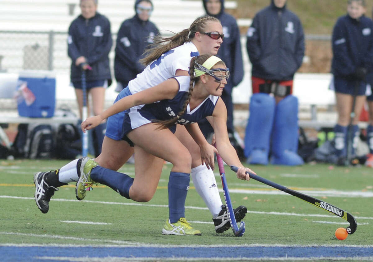 Hour photo/John Nash Staples' Meg Fay, front, beats Glastonbury's Leyna DeMarco to the ball during the first half of Saturday's CIAC Class LL quarterfinal field hockey game. Glastonbury won the game 1-0.