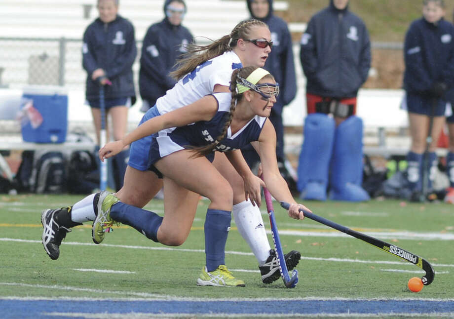 Hour photo/John NashStaples' Meg Fay, front, beats Glastonbury's Leyna DeMarco to the ball during the first half of Saturday's CIAC Class LL quarterfinal field hockey game. Glastonbury won the game 1-0.
