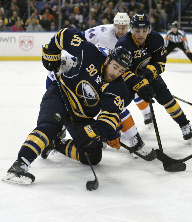 Buffalo Sabres center Ryan O'Reilly (90) wins a face-off as New York Islanders defenseman Calvin de Haan (44) and Sabres center Sam Reinhart (23) look on during the first period of an NHL hockey game, Thursday Dec. 31, 2015 in Buffalo, N.Y. (AP Photo/Gary Wiepert)