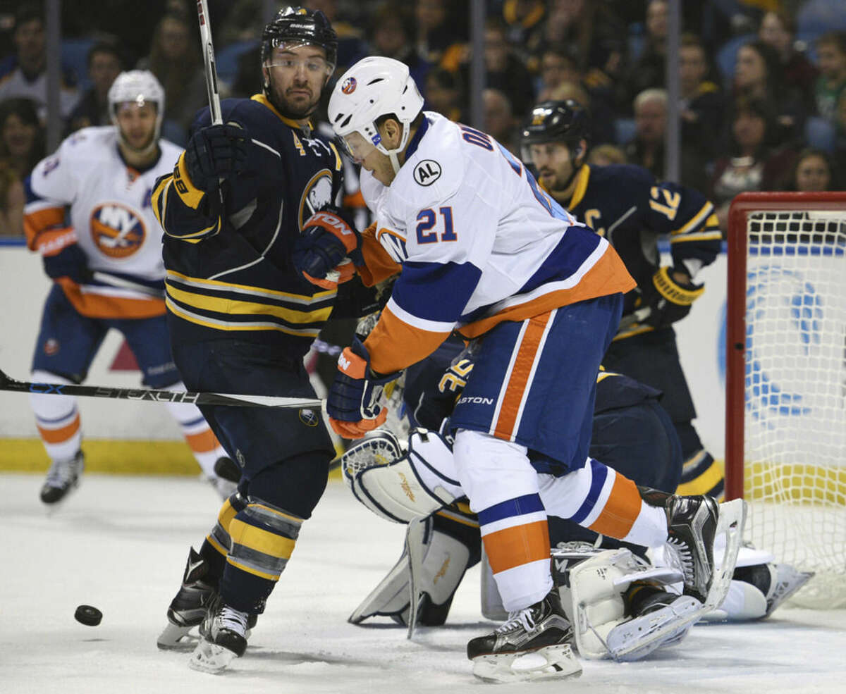 Buffalo Sabres defenseman Josh Gorges (4) battles for the puck with New York Islanders right winger Kyle Okposo (21) during the second period of an NHL hockey game, Thursday Dec. 31, 2015 in Buffalo, N.Y. (AP Photo/Gary Wiepert)