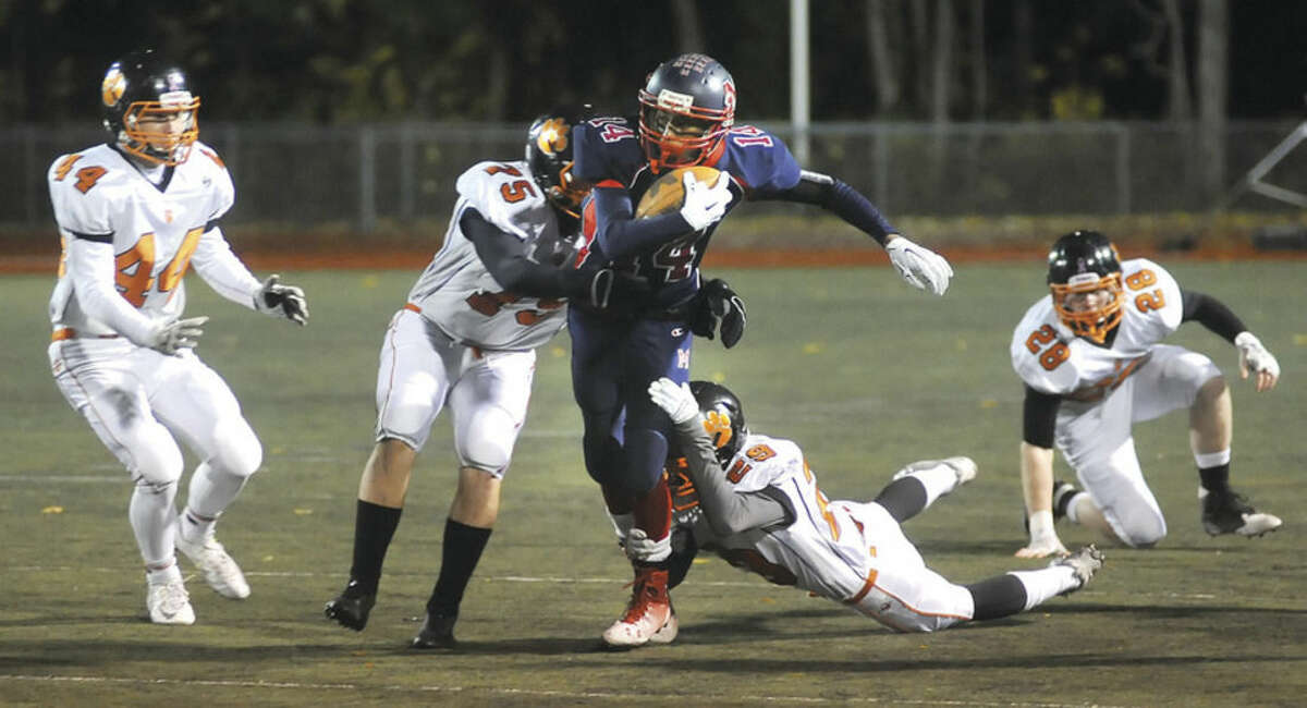 Hour photo/John Nash Tyre Holman of Brien McMahon, center, is pursued by a bunch of Ridgefield Tigers during Friday night's home game at Casagrande Field.
