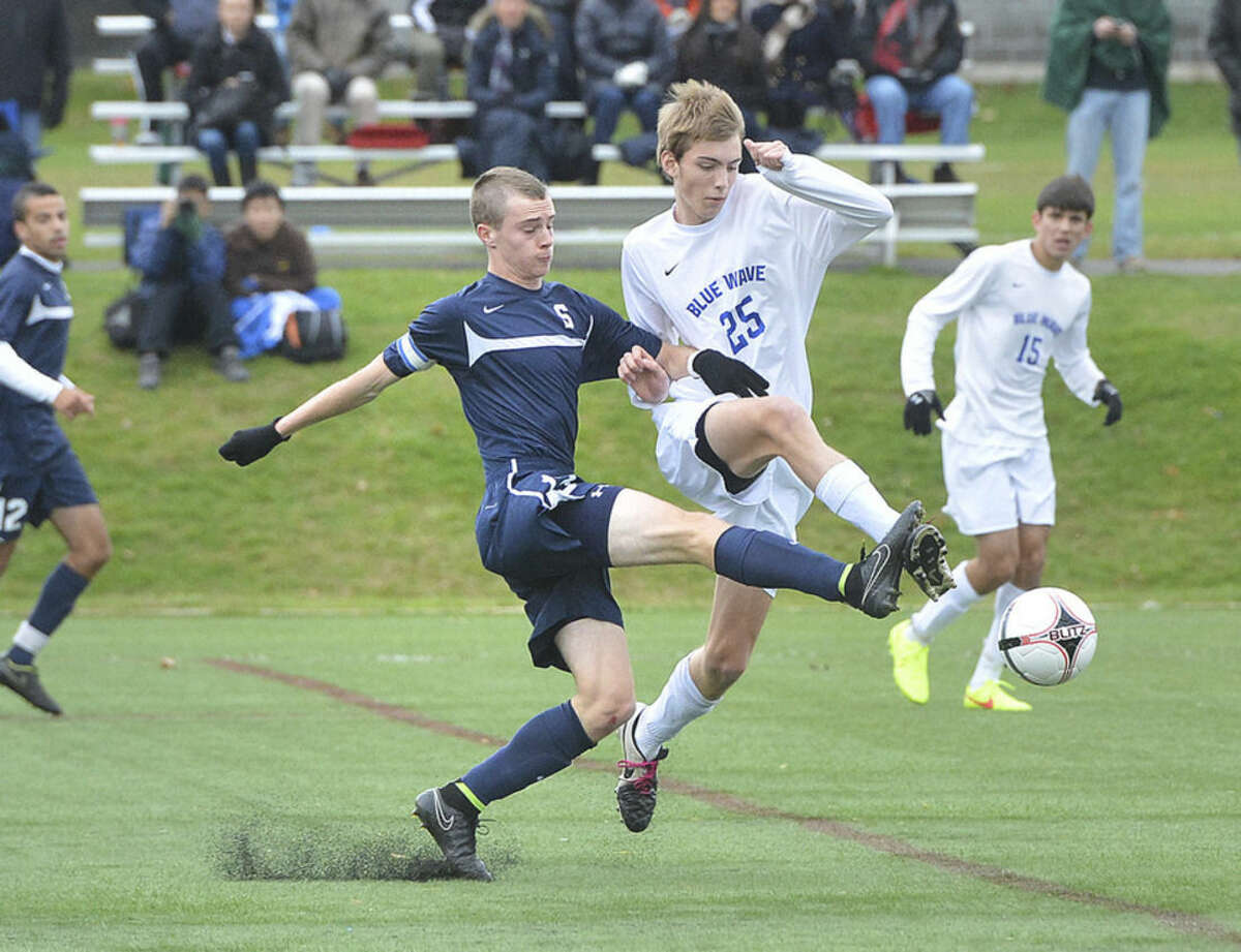 Hour photo/Alex von Kleydorff Staples' Patrick Beusse, left, and Darien's Sam Pfommer race for a ball during Friday's Class LL state tournament game.