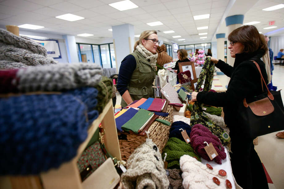 Hour photo/Chris Palermo. Kate Hutton, of K.M. Hutton Modern Stitchery, shows a customer some of her items at the CraftWestport pop-up marketplace at Staples High School Saturday.