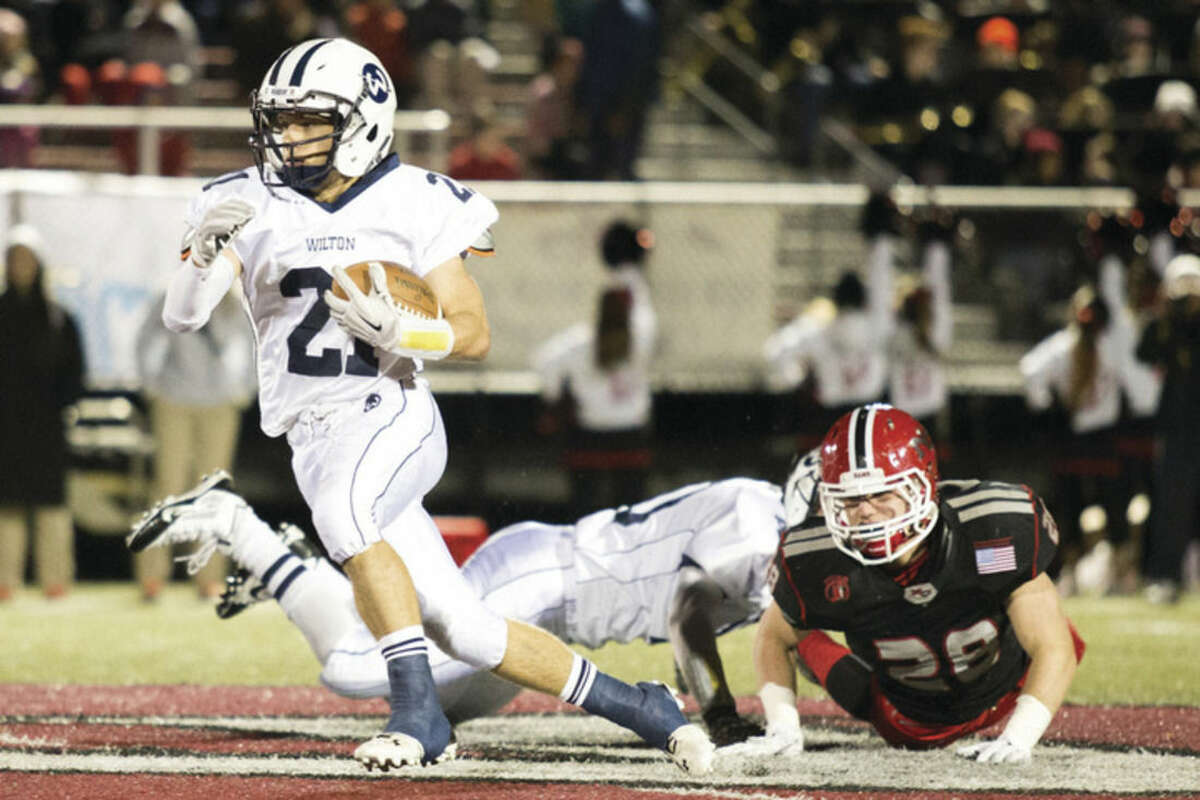 Hour photo/Chris Palermo Wilton's Patrick Ryan advances the ball upfield during New Canaan's win over Wilton Friday night.
