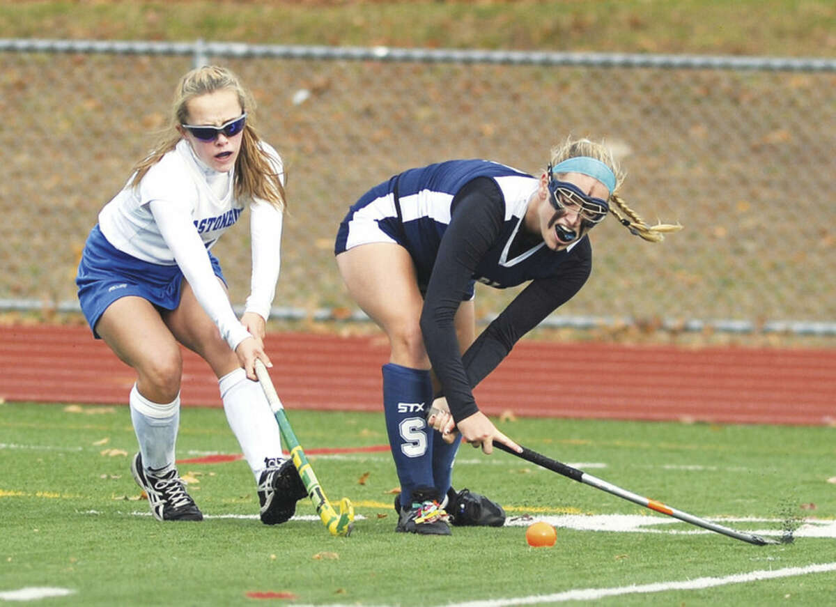 Hour photo/John Nash Staples' Jenna McNicholas, right, hits the ball up field against Glastonbury defender Bryn Murray during Friday's CIAC Class L quarterfinal in Glastonbury.