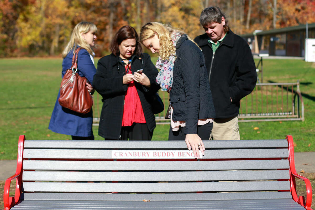 Hour photo/Chris Palermo. Beata Palosz touches the bench dedicated to her late brother Bartlomiej Palosz after a dedication ceremony held for Bart at Cranbury Elementary School Saturday morning.