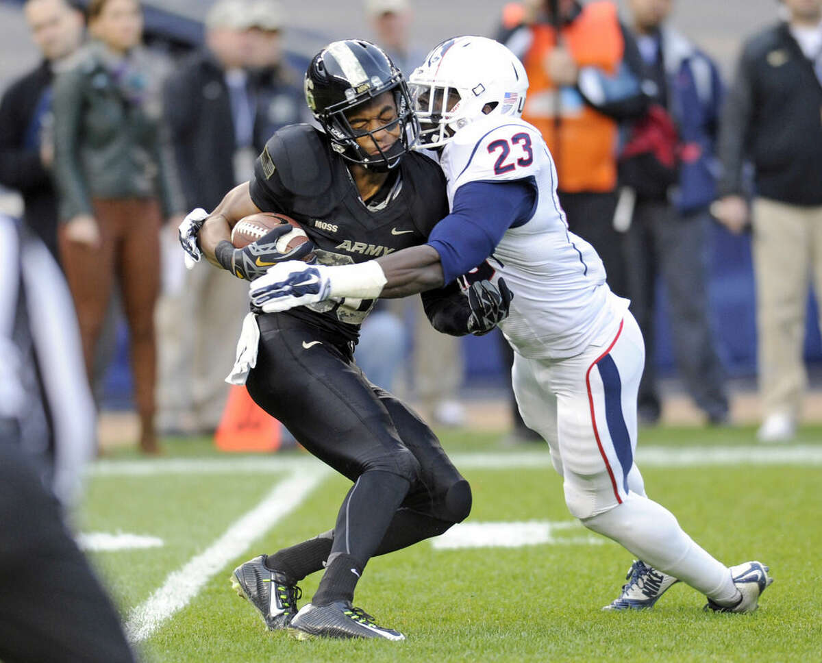 Connecticut safety Wilbert Lee, right, stops Army wide receiver Xavier Moss during the first half of an NCAA college football game Saturday, Nov. 8, 2014, at Yankee Stadium in New York. (AP Photo/Bill Kostroun)