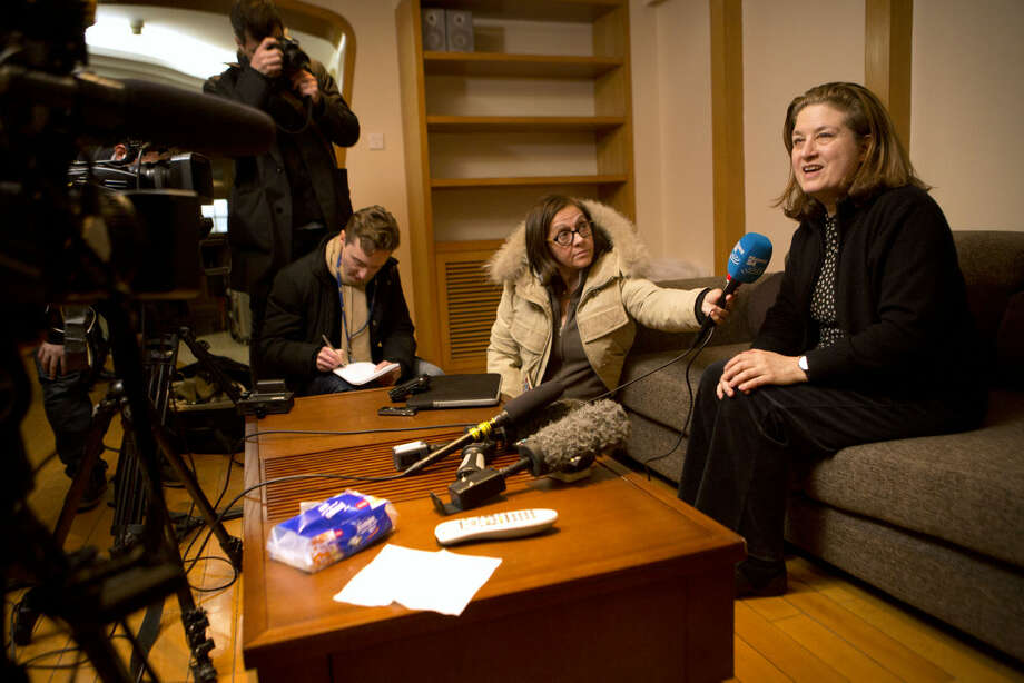 French journalist Ursula Gauthier, right, a reporter in China for the French news magazine L'Obs, speaks to the media in her apartment before leaving for the airport in Beijing, Thursday, Dec. 31, 2015. Gauthier is leaving China after being denied press credentials and facing heavy criticism from the Foreign Ministry and state media over her reporting, becoming be the first foreign journalist forced to leave China since 2012, when American Melissa Chan, then working for Al Jazeera in Beijing, was expelled. (AP Photo/Mark Schiefelbein)