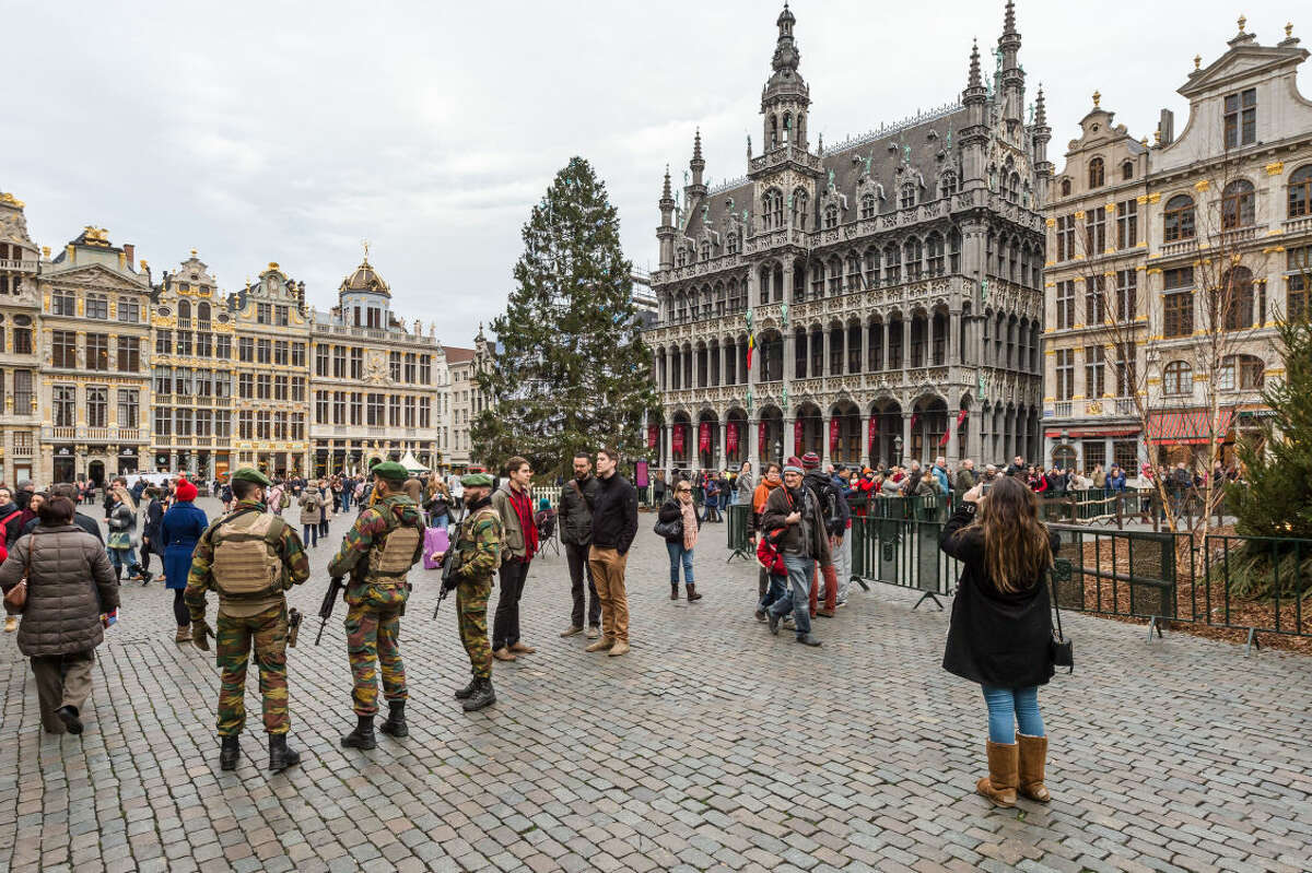 Belgian soldiers patrol as tourists visit the Grand Place in Brussels on Tuesday, Dec. 29, 2015. Two people have been arrested in Belgium on suspicion of planning attacks in Brussels during the holidays, the federal prosecutor's office said Tuesday. A source close to the investigation said the Belgian capital's main square, thronged this time of year with holiday shoppers and strollers, was one of the suspected targets. (AP Photo/Geert Vanden Wijngaert)